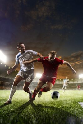 Canvas print Soccer players in action on sunset stadium background