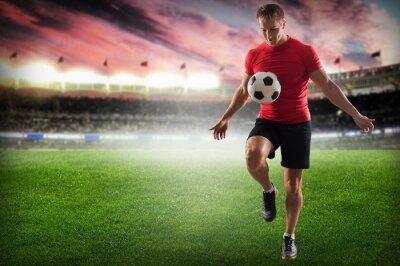 Canvas print Soccer. Professional soccer player kicking ball