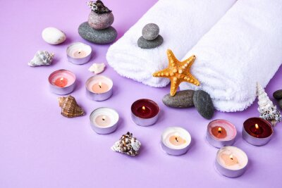 Spa still life treatment with candles, stones, sea shells starfish and towels on pink background