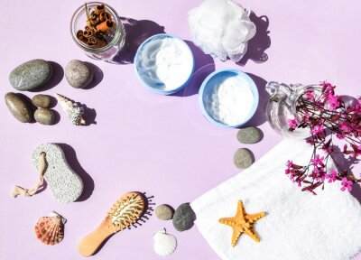 Spa still life treatment with candles, stones, sea shells starfish and towels on pink background, skincare products, natural cosmetics for home spa treatment