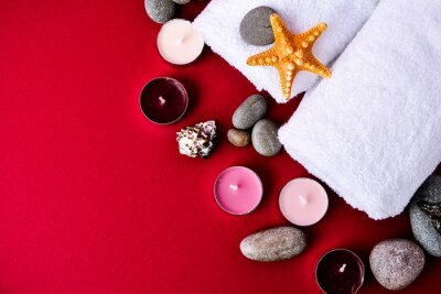 Spa still life treatment with candles, stones, sea shells starfish and towels on red background