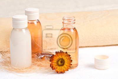 Spa still life with essential oils, towels and a flower