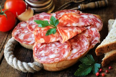 Canvas print Spanish tapas - sliced salame on rustic wooden cutting board with bread and tomatoes