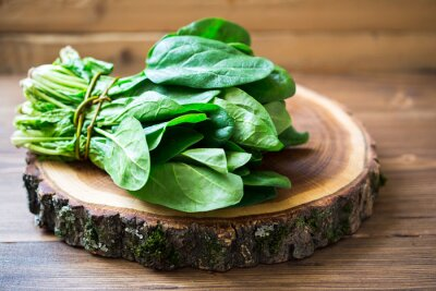 Canvas print Spinach leaves on wooden circle