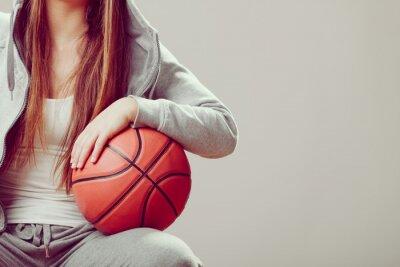 Canvas print Sporty teen girl in hood holding basketball.