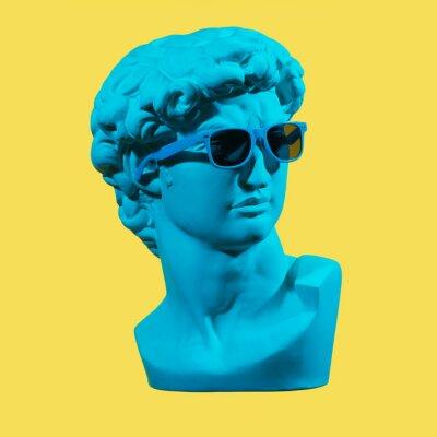 Canvas print Statue. Earphone. Isolated. Gypsum statue of David's head. Man. Creative. Plaster statue of David's head in blue sunglasses. Minimal concept art.