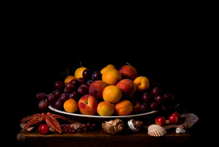 Still life in vintage style, fruit dish surrounded by sea shells, starfish and berries, isolated on black background