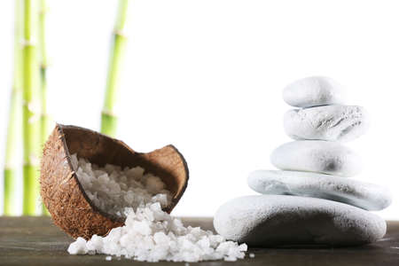 Still life of spa stones and coconut shell of sea salt on wooden surface with bamboo sticks isolated on white