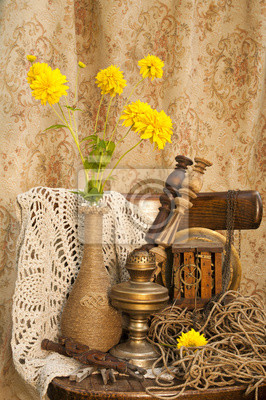 still life with clockwork oil lamp and yellow flowers