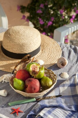Still life with fruits, hat and sea shells in the sunlight