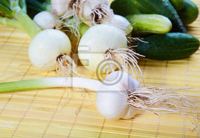 Still-life with onions garlic and green cucumbers on a table