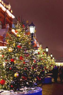 Streets in the historical center of Moscow decorated for New Year and Christmas celebration. Fir trees with bright red and yellow balls and light bulbs. Russia.