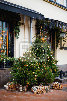 Streets of Moscow decorated for New Year and Christmas celebration. Fir trees with golden balls and light bulbs. Russia.