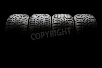 Canvas print Studio shot of a set of four black car tires lined up horizontally in a dark ambient on black background