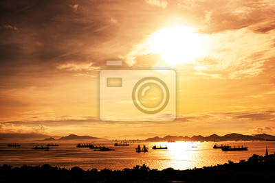 Sunset at sea with silhouettes boat fishing