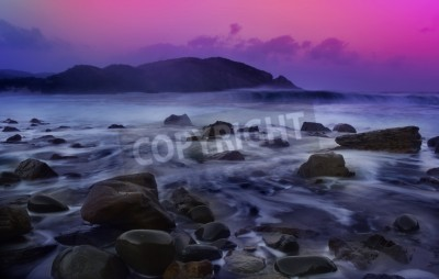 sunset at sea with waves and rocks