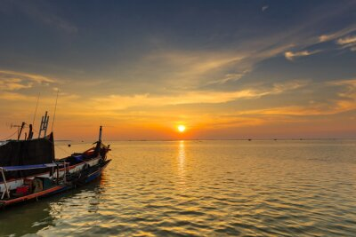 Sunset over sea with boat and shell farm