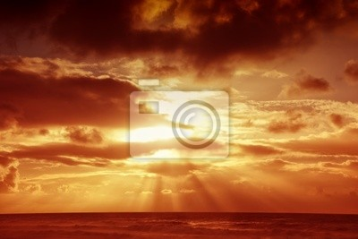 sunset over sea with moody sky, dark storm clouds, and red light