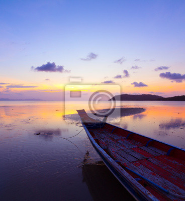 Sunset over sea with small wooden boat, Thailand