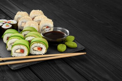 Canvas print Sushi rolls with avocado, salmon and sesame seeds on slate tray.