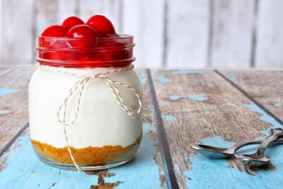 Canvas print Sweet cherry cheesecake in a mason jar on a rustic wood background