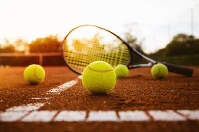 Canvas print Tennis balls with racket on clay court