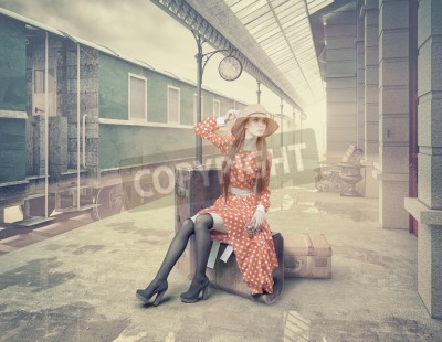 Canvas print The girl sitting on the suitcase waiting at the retro railway station. Vintage color cards style