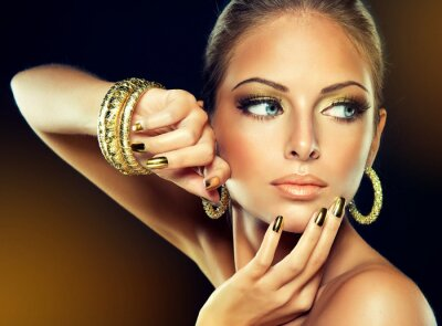 Canvas print The girl with the Golden makeup and metal nails.