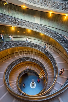 Tourists walk down the famous spiral staircase with beautiful rails in Vatican Museum.