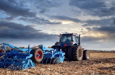 Canvas print Tractor working in the field at sunset