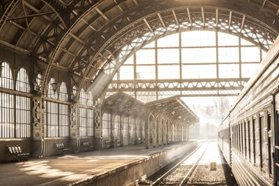 Canvas print Train station indoor sunset sunrise in sepia. Carriage and platform with construction roof. Travel on train on railway
