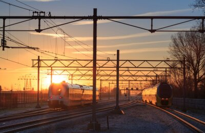 Canvas print Trains leaving a station during a winter sunrise.