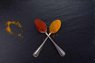 Canvas print Two vintage spoons with spices curry and paprika on black background.