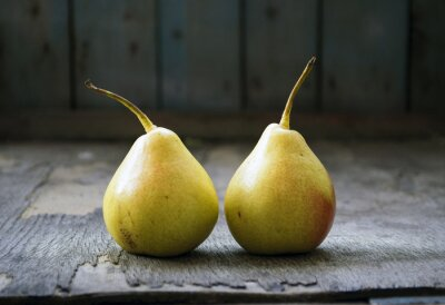 Canvas print Two yellow pear twins on wooden floor, still life