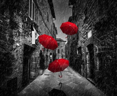 Canvas print Umrbellas flying with wind and rain on dark street in an old Italian town in Tuscany, Italy