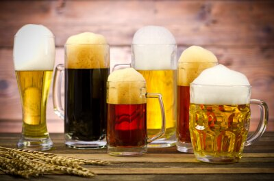 Canvas print Variety of beer glasses on a wooden table