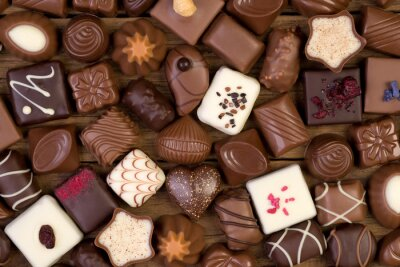 Canvas print Various chocolates on wooden background