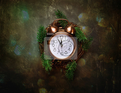 Vintage Copper Alarm Clock Five Minutes to Midnight New Years Countdown Christmas Wreath Fir Tree Branches on Black Background Glittering Lights Greeting Card Copy Space