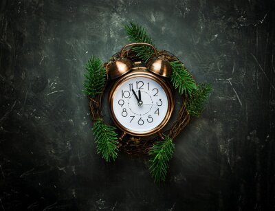 Vintage copper Alarm Clock Five Minutes to Midnight New Years Countdown Christmas Wreath Fir Tree Branches on Black Background Greeting Card Copy Space