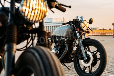 Canvas print Vintage custom motorcycle cafe racer motorbike with lamp lights turned on. One with grill headlight another with tape cross over optic on empty rooftop parking lot during sunset. Hipster lifestyle.