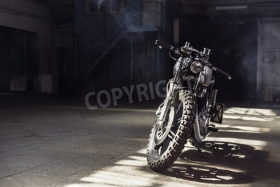 Canvas print Vintage motorcycle standing in a dark building in the rays of sunlight. Toned colors. Front view