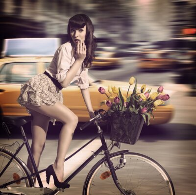 Canvas print vintage woman on bicycle in a city street with taxi