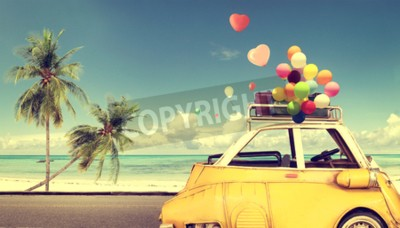 Canvas print Vintage yellow car with heart colorful balloon on beach blue sky - concept of love in summer and wedding. Honeymoon trip