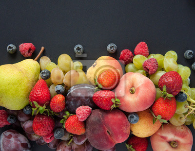Vitamin fruits and berries are natural products. Pears, apples, plums, grapes, strawberries, raspberries, blueberries, peaches on a black background. Natural vitamins and minerals. Vegan eco food.