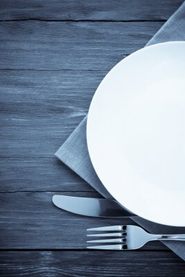 Canvas print white plate, knife and fork on wood