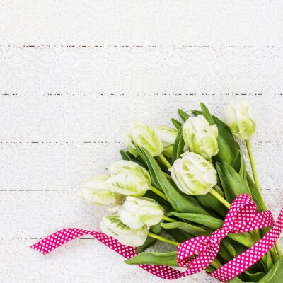 Canvas print White tulips decorated with red ribbon on white tablecloth. Copy space, top view