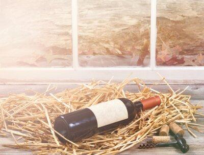 Canvas print Window light on wine bottle resting in straw