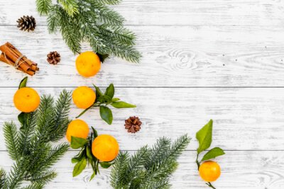 Winter fruits for New Year and Christmas. Tangerines, fir tree and cinnamon on white wooden background top view mock-up