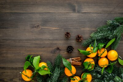Winter fruits for New Year and Christmas. Tangerines, fir tree and cinnamon on wooden background top view mock-up