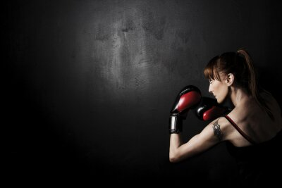 Canvas print Woman Boxer with Red Gloves on Black Background, high contrast with desaturated grunge filter in studio